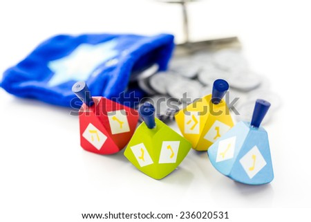 Colorful dreidels with silver tokens on a white background - stock photo