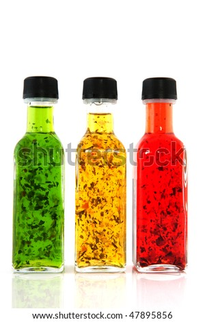 Colorful dressing with herbs in glass bottles - stock photo