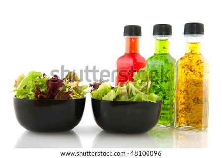 Colorful dressing with herbs in glass bottles with salad - stock photo