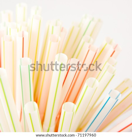Colorful drinking straws. Close up of colored drinking straws with shallow depth of field on white background. - stock photo