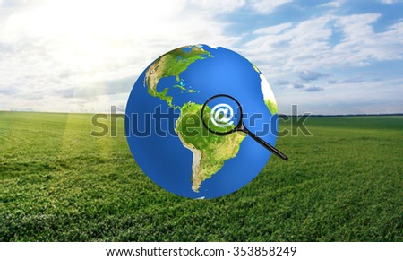 Colorful earth with magnifying glass. Elements of this image furnished by NASA - stock photo