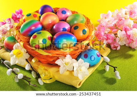 Colorful easter basket with painted easter eggs, narcissus and catkin - stock photo