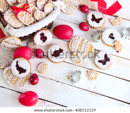 Colorful Easter cookies in a basket and red easter eggs on a white background wooden