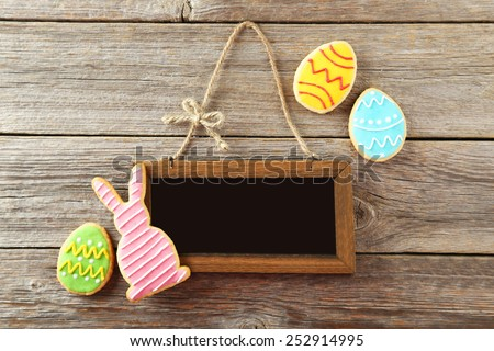 Colorful easter cookies with frame on grey wooden background - stock photo