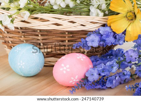 Colorful Easter decoration with colored eggs, flowers and basket - stock photo