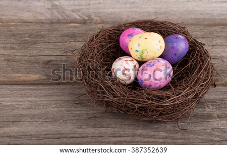 Colorful Easter egg candy in a nest on an old wooden background