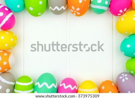 Colorful Easter egg frame around a white wood background - stock photo