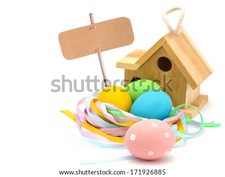 Colorful easter eggs  and bird house with empty tag isolated on white background. Selective focus. - stock photo