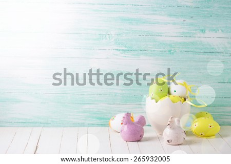 Colorful easter eggs and hens  in ray of light on mint wooden background. Easter background.Toned image.Selective focus. - stock photo