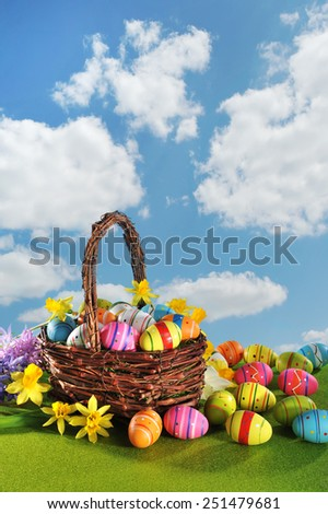 colorful easter eggs and narcissus in easter nest on grass with sky - stock photo