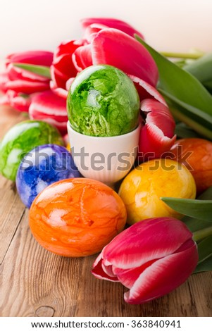 Colorful easter eggs and pink tulips on wooden background. Selective focus. Spring holidays concept.