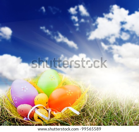 Colorful Easter eggs decorated in the grass on blue sky background