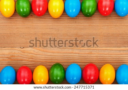 Colorful easter eggs framing an old wooden table surface - with copy space - stock photo