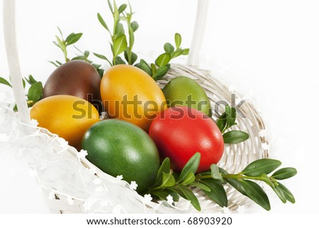 Colorful Easter eggs in a basket. - stock photo
