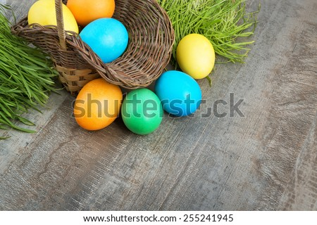 Colorful Easter eggs in a basket and green grass on a wooden table with copy space for text greetings - stock photo