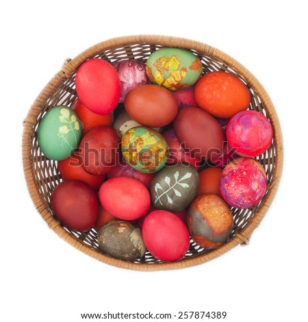 Colorful Easter Eggs in a Basket, on White Background Top View - stock photo
