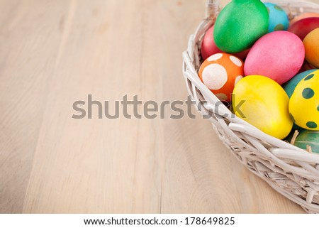 colorful easter eggs in a basket on wooden background - stock photo