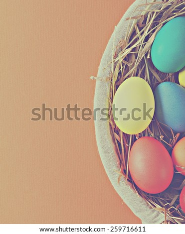 colorful easter eggs in a basket with hay. toning in retro style - stock photo
