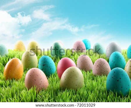 Colorful Easter eggs in a field of grass with blue sky - stock photo