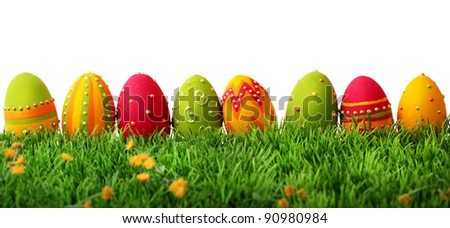 Colorful easter eggs in a row on green grass - stock photo