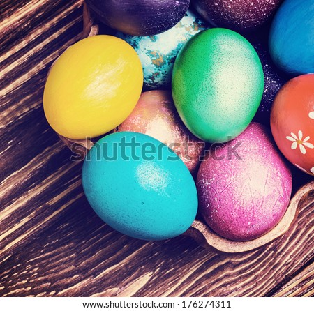 Colorful easter eggs in a wooden plate. toned photo - stock photo