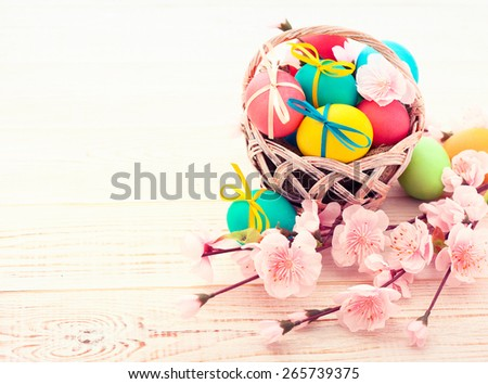 Colorful easter eggs in basket and branch with flowers. Selective focus - stock photo