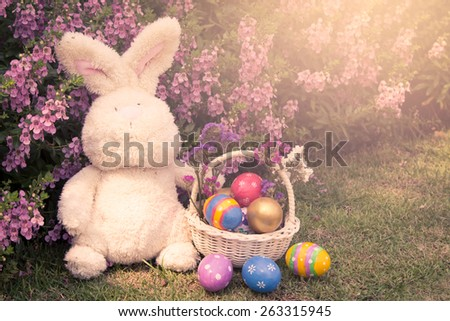 Colorful easter eggs in basket with cute rabbit on flower background in soft color - stock photo