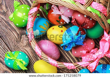 Colorful easter eggs in brown basket - stock photo