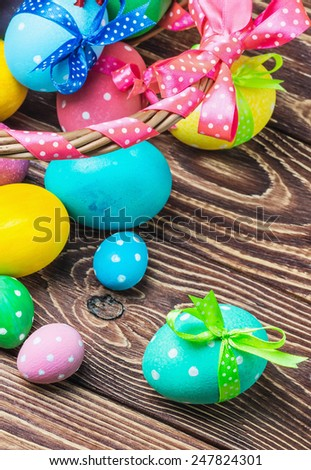 Colorful easter eggs in brown basket. Focus on a green egg in the foreground - stock photo