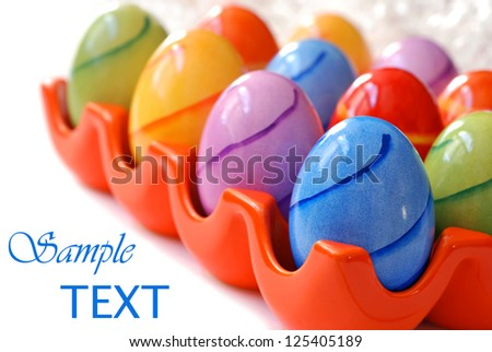 Colorful easter eggs in ceramic tray on white background with copy space.  Macro with shallow dof.  Selective focus on blue egg. - stock photo