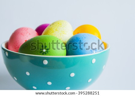 Colorful easter eggs in green spotted bowl on light background.