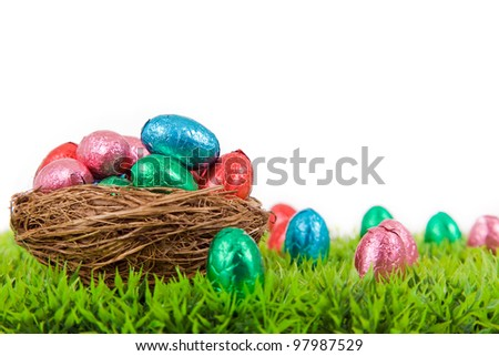 Colorful Easter eggs in nest on fresh grass, isolated on white