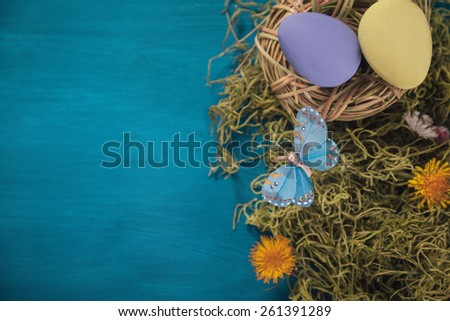 Colorful Easter eggs in nest on the grass with yellow dandelions with copy space - stock photo