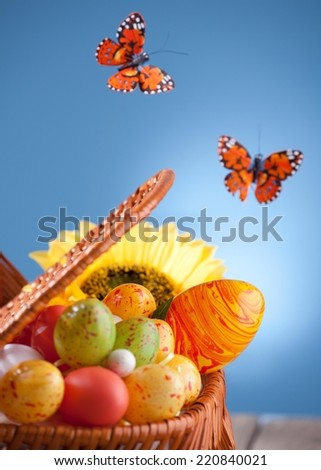 Colorful Easter eggs in the basket. Butterflies flying around. - stock photo