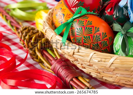 Colorful Easter Eggs in the basket with wicker and bows, traditional decoration for this spring holiday