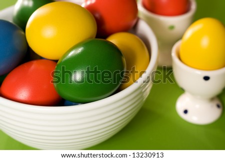Colorful Easter Eggs in white bowl on green background