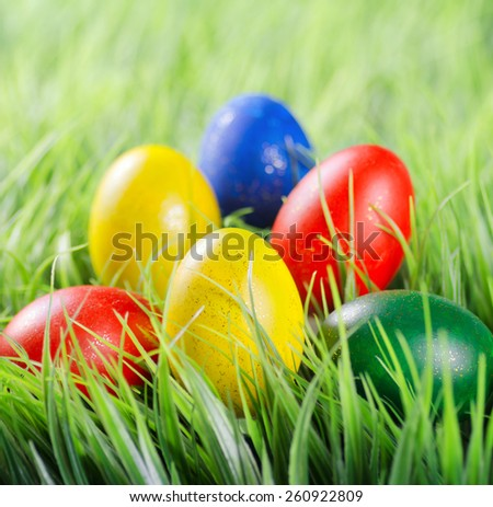 Colorful Easter eggs lying in a pyramid shape on green grass in the morning. Yellow, red, green and blue eggs painted for the Easter. Organic healthy eco food rich in minerals and vitamins. - stock photo