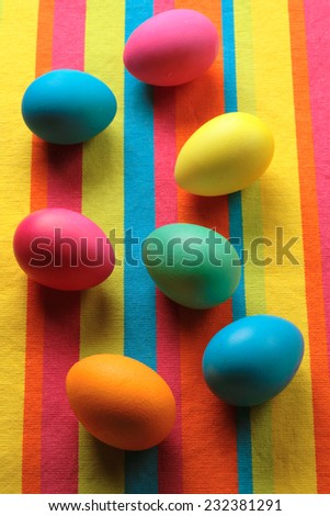Colorful Easter eggs on a striped cloth - stock photo