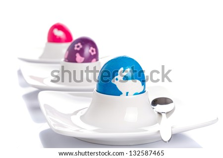 Colorful Easter eggs on plates with spoons - stock photo
