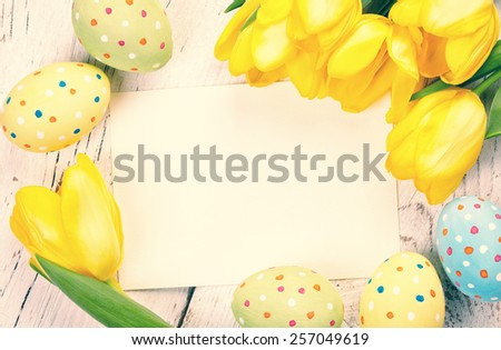 Colorful Easter eggs, tulips and blank card on wooden background - stock photo