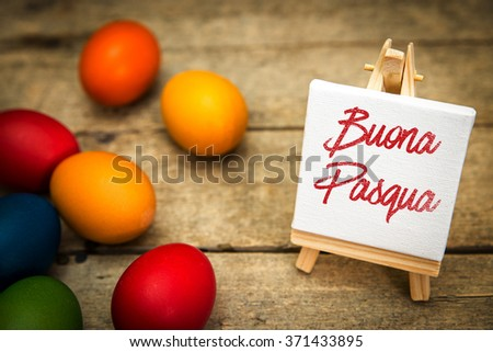 colorful easter eggs with canvas and italian text, buona pasqua, which means happy easter, wooden background - stock photo