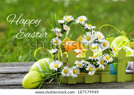Colorful easter eggs with daisies on wood - stock photo