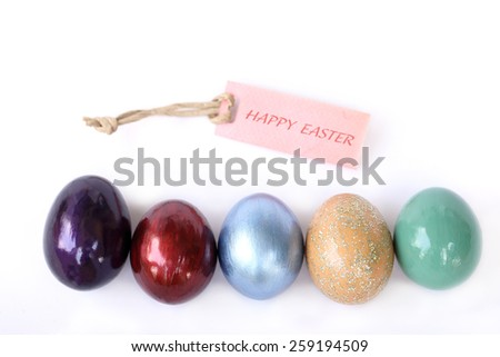 Colorful easter eggs with Happy easter text on paper tag over white background. - stock photo