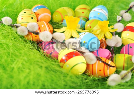 colorful easter eggs with narcissus and catkin in green sisal.