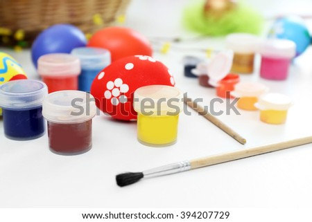 Colorful Easter eggs with paints on table closeup