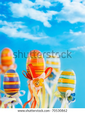 Colorful easter eggs with ribbons on blue sky background