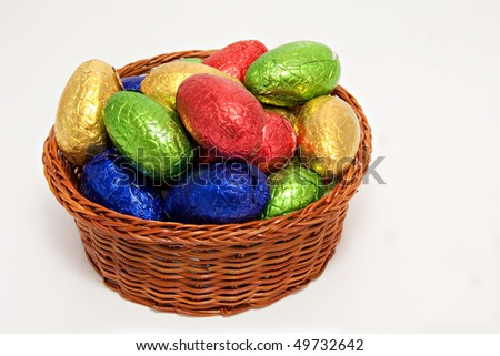 colorful easter eggs wrapped in shiny foil in wicker basket white background