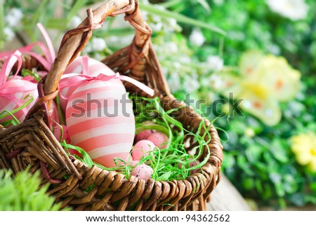 Colorful Easter holiday concept with pink eggs in wisker basket in nature - stock photo