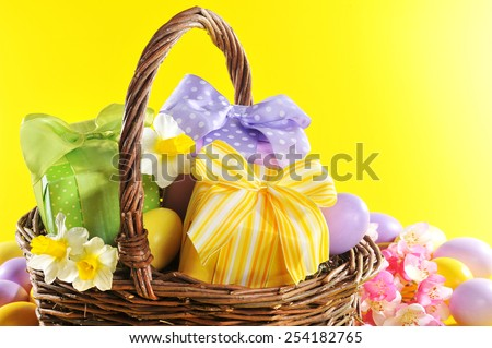 colorful easter presents with bow in easter basket with narcissus and painted easter eggs - stock photo
