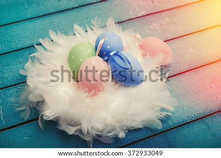 Colorful eggs decorated with white fur on table - stock photo